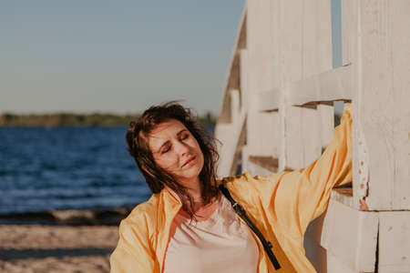 Nice plus size woman in a yellow jacket rests on a white wooden structure on a sandy beach