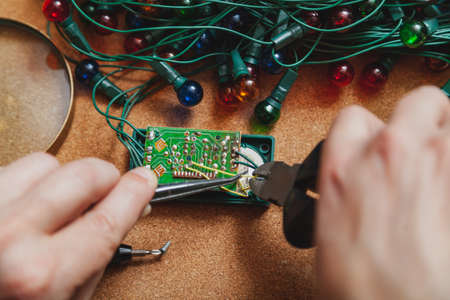 Preparing for the New Year. Repair of a fir-tree electric garland. In the hands of an electrician, clippers and tweezers