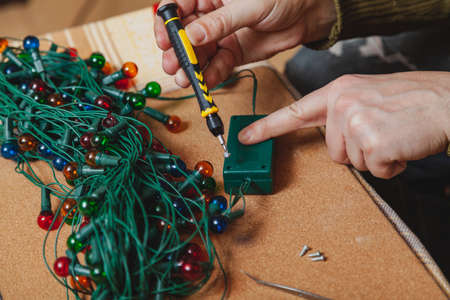 Preparing for the New Year. Repair of a Christmas tree electric garland. Hands open the control box box with a screwdriver