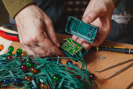 Preparing for the New Year. Repair of a Christmas tree electric garland. Hands opened the box of the control unit