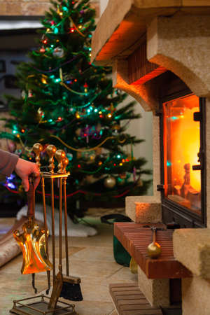 New Year interior. A fireplace tool kit stands in front of a burning fireplace. The garlands on the Christmas tree glow in the back