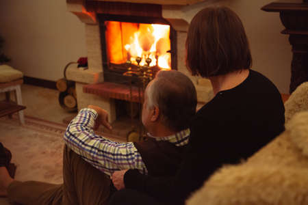 Christmas in a cozy home environment. An elderly man sits on a carpet in front of the fireplace. A pretty elderly woman hugs him. A Christmas wreath hangs over the fireplace Reklamní fotografie