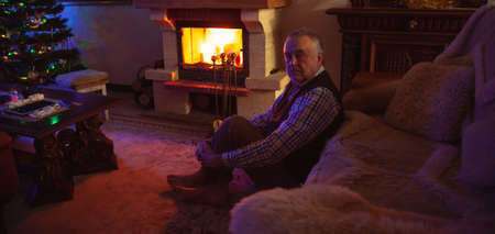 New Year Eve by the fireplace. An elderly man sits on a carpet in front of a fireplace in a dark room. A fire burns brightly in the fireplace. There is a decorated Christmas tree in the corner of the room Reklamní fotografie