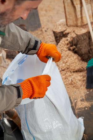Hands in orange gloves hold a white plastic trash bag