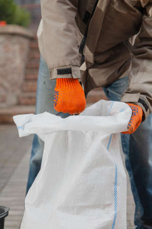 Worker in orange gloves tamping garbage in a plastic bag in the yard