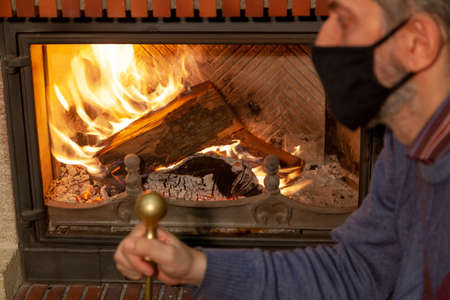 We are sitting at home on self-isolation. A man in a black protective mask looks at the fire in the burning fireplace. Holds a poker in his hand