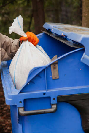 We collect garbage in the bin. Man puts filled bag in blue garbage container