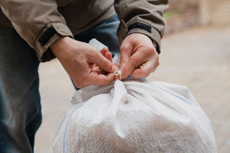 Hands tying rope on white plastic bag close up