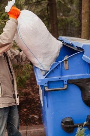 Man puts filled bag in blue garbage container Reklamní fotografie