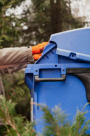 Hand in work gloves opens the lid of a blue plastic waste bin