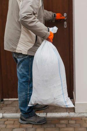 Man carries full plastic garbage bag in clean yard
