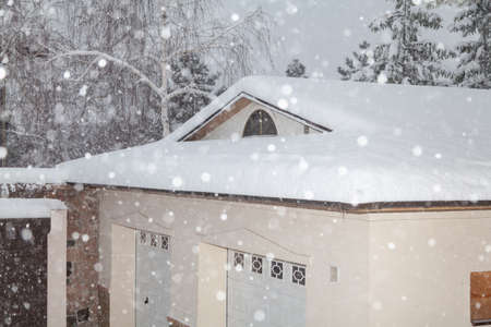 Snowfall in the yard. White snow lies in the yard and on the roof of the one-story building. Thick snow is flying from above