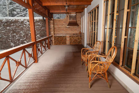 Winter plot. Two rattan wicker chairs sit on an empty veranda. White snow lies on the railing and the floor