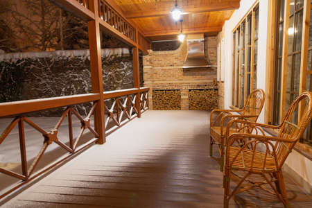 Winter evening on the veranda. Two rattan wicker chairs sit on an empty veranda. White snow lies on the railing and floor. Two pendant lights are shining
