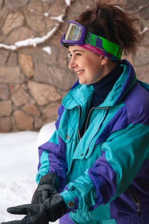 nice girl in a ski jumpsuit stands in a snowy courtyard against a stone fence. Portrait of a woman without retouching with her natural imperfections