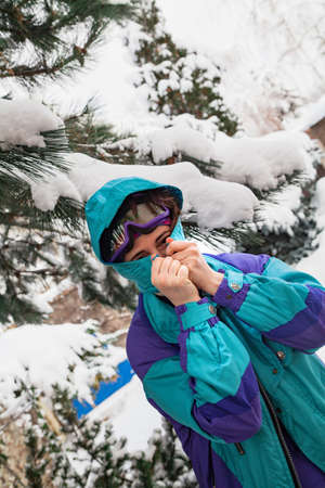 beautiful young woman in a ski overalls puts on a hood under a tall pine tree. There is snow on the pine branches