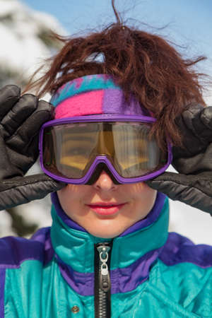 Beautiful young woman in ski overalls. Hands in winter gloves adjust ski goggles. A female portrait without retouching with her natural imperfections Reklamní fotografie