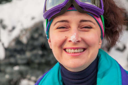 beautiful young woman in ski goggles smiles happily. There is white snow on the woman's nose. A female portrait without retouching with her natural imperfections