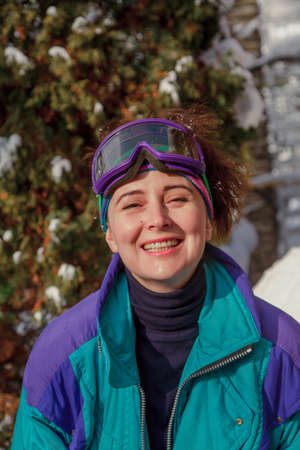 Beautiful young woman in ski overalls. On the head are sports glasses. A female portrait without retouching with her natural imperfections