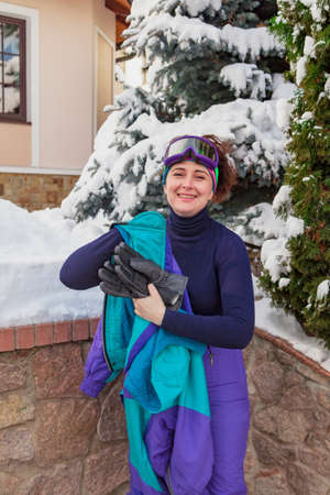 Beautiful young woman in ski goggles stands in a winter yard and takes off her jacket