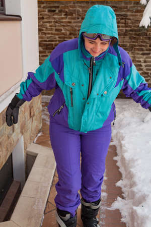 Beautiful young woman in ski overalls and boots walks along the wall of the house. White snow lies on the right.