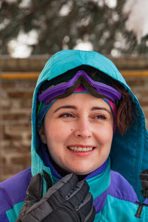 Beautiful young woman in a ski overalls in a hood. A female portrait without retouching with her natural imperfections