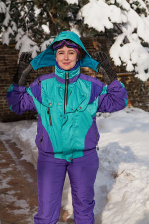 beautiful young woman in ski goggles and overalls stands against the backdrop of tall trees. The snow is white. A female portrait without retouching with her natural imperfections