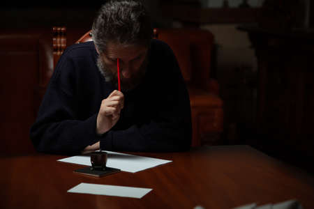 man with a beard sits at a large polished table and ponders over a white sheet. In his hand is a wooden pen with a metal nib. There is a metal inkwell nearby