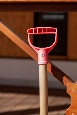 Red plastic handle of snow shovel on wooden handle close up