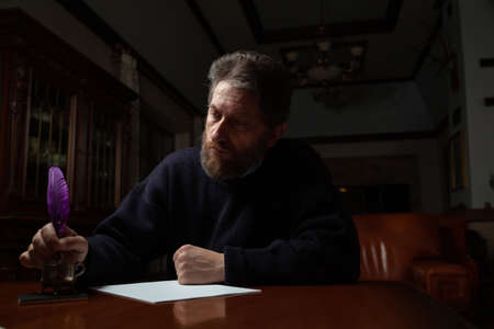 man with a beard sits at a large polished table and writes on a white sheet using a goose feather and inkwell