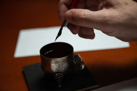 Vintage writing instrument. The right hand lowers the wooden pen with the metal pen into the inkwell. Left hand holds a white sheet of paper