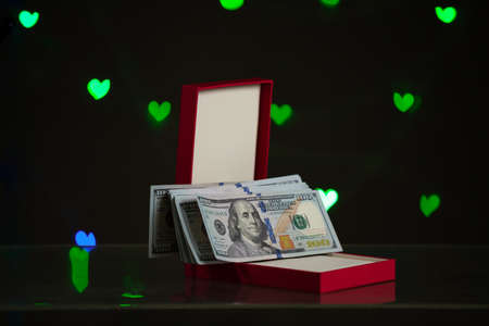 Valentine's Day gift. An open red gift box stands against a dark background. It contains a bundle of dollar bills. Green hearts glow in the back
