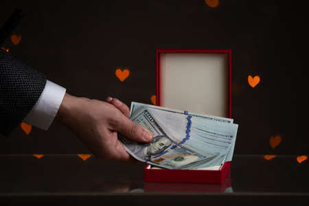 Valentine's Day gift. A hand puts a bundle of dollars in a red box. Yellow hearts are glowing behind on a dark background