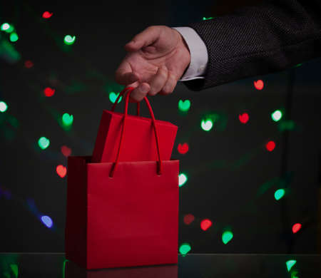 gentleman hand holds a red paper bag with a red gift box. Green and red hearts are glowing behind on a dark background