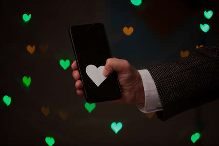original gift for Valentine's Day. The right hand holds a mobile phone. A white paper heart presses on top of the phone. Green and yellow hearts are glowing behind on a dark background