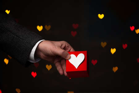 original gift for Valentine's Day. A hand in a jacket and white shirt holds a red box. He presses a heart made of white paper from above. Red and yellow hearts glow on the back on a dark background