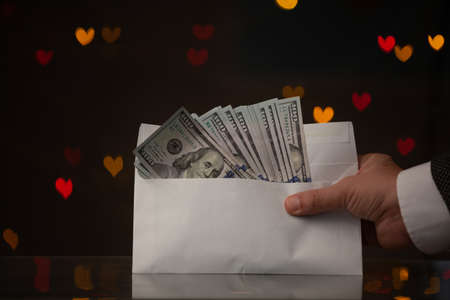 Valentine's Day gift. A hand in a jacket and white shirt holds an envelope with dollar bills. Behind on a dark background red and yellow hearts, hand, bill, money, gift,