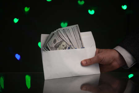 Valentine Day gift. A hand in a jacket and white shirt holds an envelope with dollar bills. Behind on a dark background green hearts