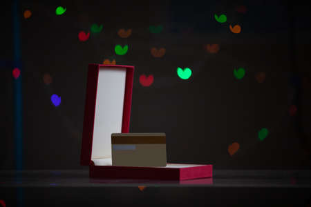 Valentine's Day gift. A plastic bank card stands in a red cardboard box on a dark background with multicolored hearts