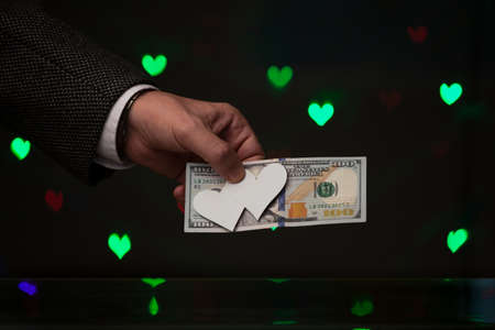 original gift for Valentine's Day. A hand in a jacket and white shirt holds a dollar bill. On top of the bill presses two hearts of white paper. Behind on a dark background green hearts