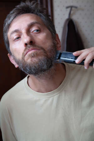 Haircut beard trimmer. A man cuts his gray beard on his own using a machine with a nozzle close-up