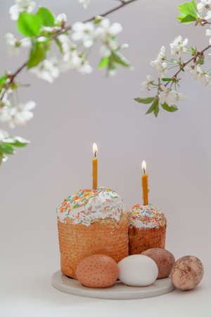 Easter still life. Two Easter cakes and eggs stand on a white background. Burning candles are inserted into the cakes. Top view of a tree branch with white flowers Stockfoto