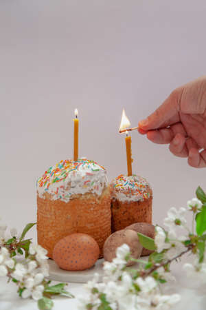 Two Easter cakes and eggs stand on a white background. Candles are inserted into the Easter cakes. A hand lights a candle with a match. In the foreground is a tree branch with white flowers