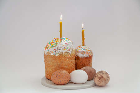 Easter still life. Two Easter cakes and eggs stand on a round stand on a white background. Burning candles are inserted into Easter cakes