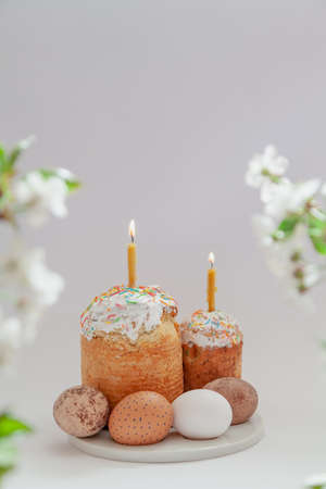 Easter still life. Two Easter cakes and eggs stand on a white background. Burning candles are inserted into the cakes. Side of a tree branch with white flowers