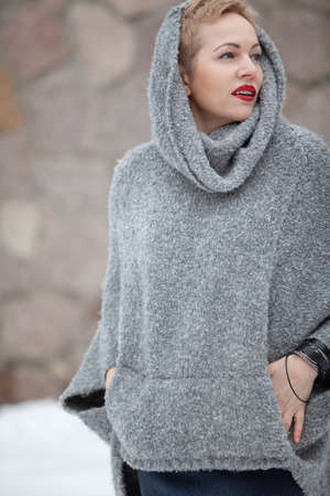 beautiful blonde in a hood and a warm sweater stands in the courtyard in the winter