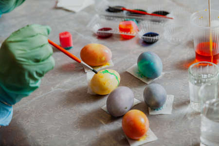 Hands in rubber blue gloves hold an egg and paint brush. Homemade painted Easter eggs and glasses with colored liquid