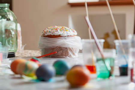 Creative Easter preparation process. Easter cake surrounded by colored eggs and containers with paints and brushes. DIY made
