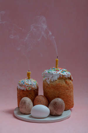 Easter still life. Two Easter cakes and eggs stand on a round stand on a pink background. Candles are inserted into the Easter cakes. Smoke visible