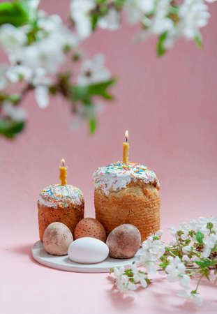 Easter still life. Two Easter cakes and eggs stand on a pink background. Burning candles are inserted into the cakes. Side of a tree branch with white flowers